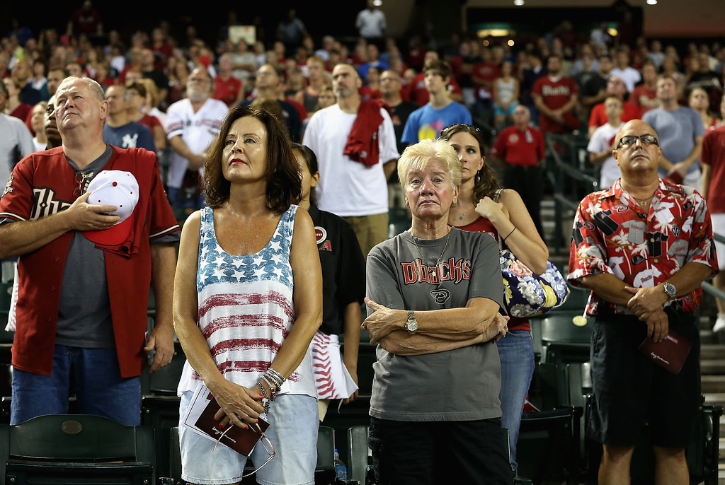""". PHOENIX, AZ - JULY 05:  Fans stand attended for the National Anthem before the MLB game between the Arizona Diamondbacks and the Colorado Rockies at Chase Field on July 5, 2013 in Phoenix, Arizona. The Arizona Diamondbacks are wearing a \""""19\"""" patch in honor of the 19 Granite Mountain Interagency Hotshot Crew firefighters who died battling a fast-moving wildfire near Yarnell, AZ.  (Photo by Christian Petersen/Getty Images)"""