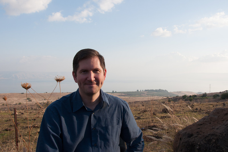 Me at the Sea of Galilee in Israel with the believed location of the Sermon on the Mount in the background.