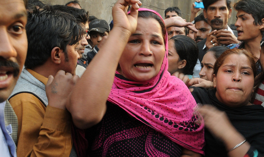 . Pakistani Christains react after Muslim demonstrators destroyed the homes of members of the Christian community during a protest over alleged blasphemous remarks by a Christian in a Christian neighborhood in Badami Bagh area of Lahore on March 9, 2013. Thousands of angry protestors on March 9 set ablaze more than 100 houses of Pakistani Christians over a blasphemy row in the eastern city of Lahore, officials said. Over 3,000 Muslim protestors turned violent over derogatory remarks allegedly made by a young Christian, Sawan Masih, 28 against Prophet Muhammad in a Christian neighboorhood in Badami Bagh area. Arif Ali/AFP/Getty Images