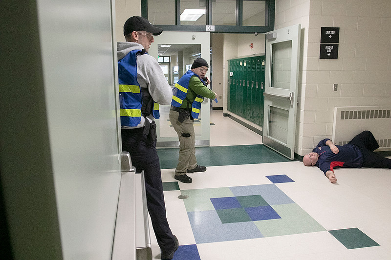 Police and firefighers from many Massachusetts departments participated in the the AAIR, Active Attack Integrated Response, class put on by ALERRT, Advanced Law Enforcement Rapid Response Training, at Sky View Middle School on Tuesday, Feb. 18, 2020. Keeping one of the hallways safe was Leominster Sgt Vang Lee, in tan pants, with Waltham officer Peter Barsam. On the floor was one of the offices in the class playing a victim that was shot.  SENTINEL & ENTERPRISE/JOHN LOVE