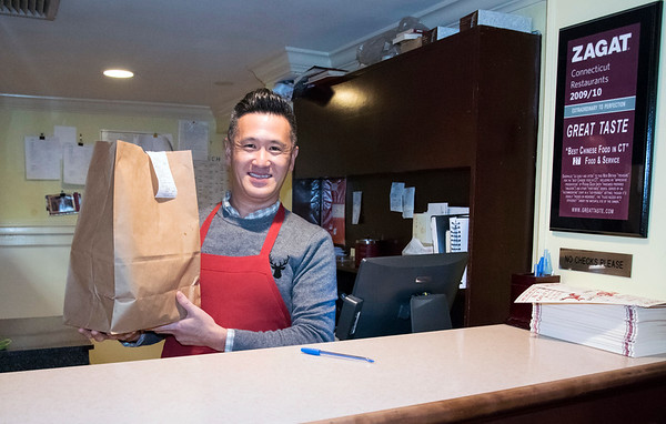 03/27/20 Wesley Bunnell | StaffrrFrank Kwok , co owner of Great Taste Restaurant, holds a to go bag up prior to ringing out a customer at his restaurant on Monday afternoon. Governor Ned Lamont ordered all restaurants closed effective at 8 p.m. with the exception of take out and delivery.