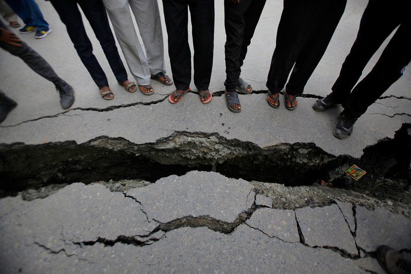 . Nepalese people look at a cracked road after an earthquake in Kathmandu, Nepal, Sunday, April 26, 2015. A strong magnitude 7.8 earthquake shook Nepal\'s capital and the densely populated Kathmandu Valley before noon Saturday, causing extensive damage with toppled walls and collapsed buildings, officials said. (AP Photo/Niranjan Shrestha)