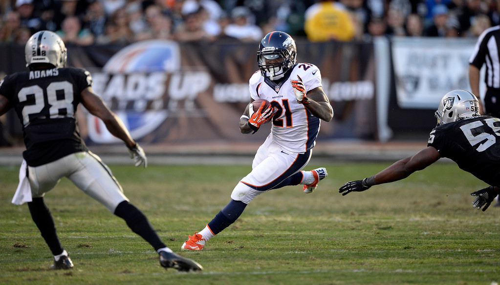 . Denver Broncos running back Ronnie Hillman (21) picks up a few yards as Oakland Raiders cornerback Phillip Adams (28) and Oakland Raiders outside linebacker Miles Burris (56) during the third quarter at O.co Coliseum. (Photo by John Leyba/The Denver Post)