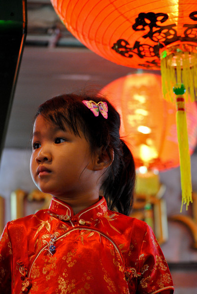 Child sits on dad's shoulders and watches the Chinese New Year festivities in Chiang Mai, Thailand.