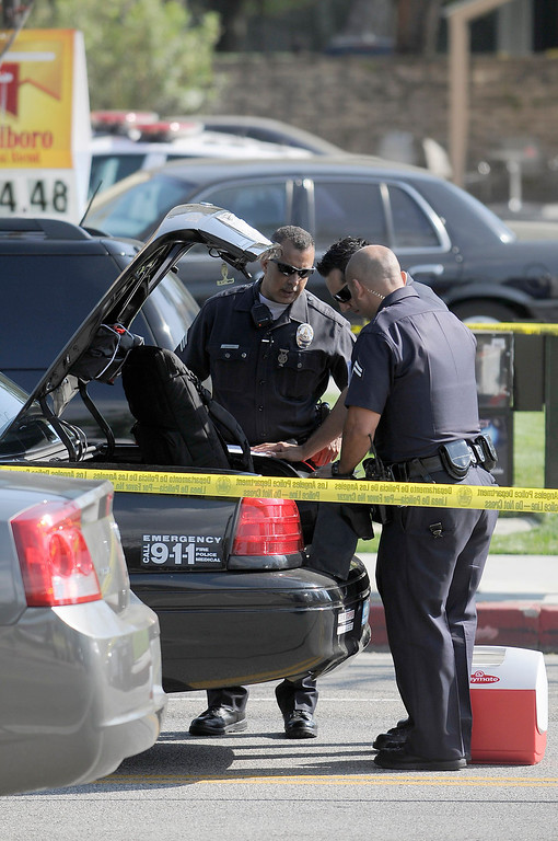 . Police officers look in the trunk of a cruiser for items to use in their investigation. A 10-year-old girl who was reported missing from her family\'s Northridge home was found safe Monday afternoon in Woodland Hills, and police said it was unclear whether she had been abducted or ran away. After an 11-hour search, Nicole Ryan was found near a strip mall about six miles from her home, Los Angeles police Capt. Kris Pitcher said. Woodland Hills,CA 3/26/2013(John McCoy/Staff Photographer