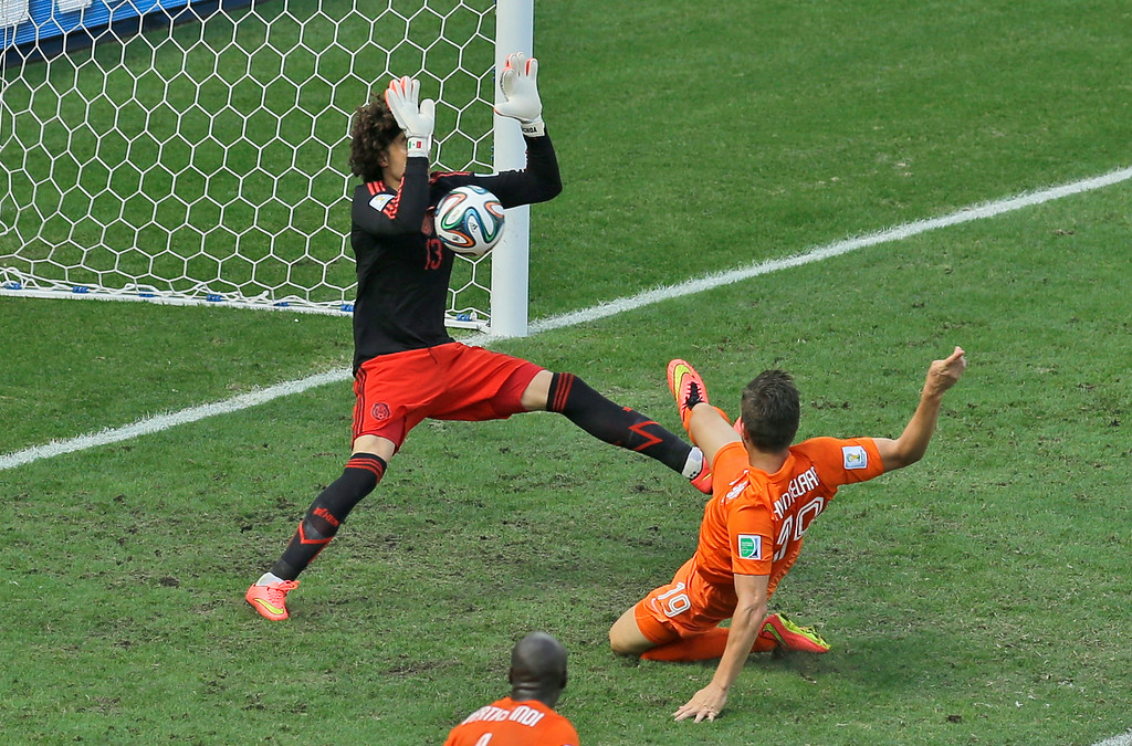 . Mexico\'s goalkeeper Guillermo Ochoa makes a save after a shot by Netherlands\' Klaas-Jan Huntelaar during the World Cup round of 16 soccer match between the Netherlands and Mexico at the Arena Castelao in Fortaleza, Brazil, Sunday, June 29, 2014. (AP Photo/Themba Hadebe)