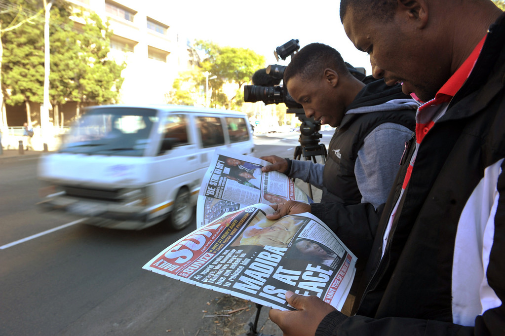 . Membes of the media reads newspapers outside the Mediclinic heart hospital  in Pretoria on June 25, 2013. Nelson Mandela spent a second night in critical condition in hospital with his family members, compatriots and well-wishers worldwide fearing that the anti-apartheid icon is about to lose his final struggle. A few vehicles were seen early on June 25, 2013 entering and exiting the Pretoria hospital where the former South African president is being treated, but otherwise the scene was quiet except for the now normal pack of journalists. ALEXANDER JOE/AFP/Getty Images