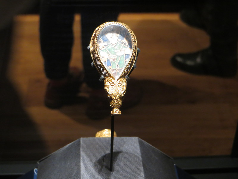 "This is the Alfred Jewel, the single most famous object in the Ashmolean.  I simply could not get a good picture of it and there were lots of people crowding around to see it, so I couldn't stand there trying .  It has been dated to the late 9th century, during the reign of Alfred the Great.  The general consensus now is that it was at one time attached to a rod, and was a pointer stick for following words while reading a book.  It's about 2 1/2 inches long and made of filigreed gold enclosing a tear-shaped piece of rock crystal with the figure of a man (perhaps Christ).  Around the sides there is a rim with the inscription: ""Aelfred mec heht gewyrcan"" (Alfred ordered me to be made).  The gold animal head base has a hollow socket.  The jewel was found on a country estate in 1693."