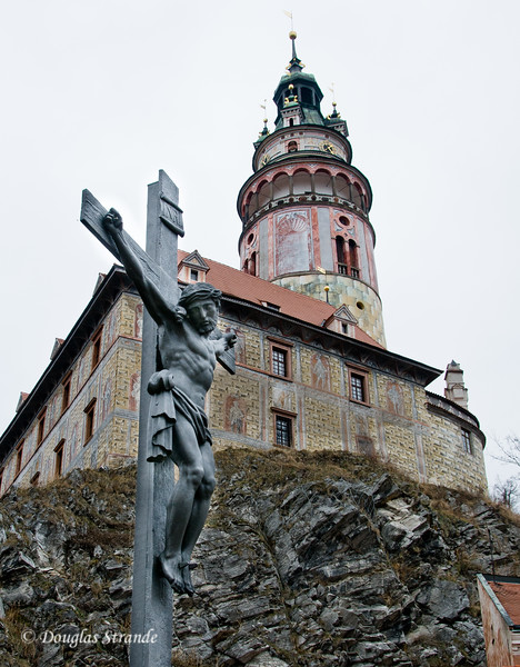 Crucifiction statue and Cesky Krumlov castle tower