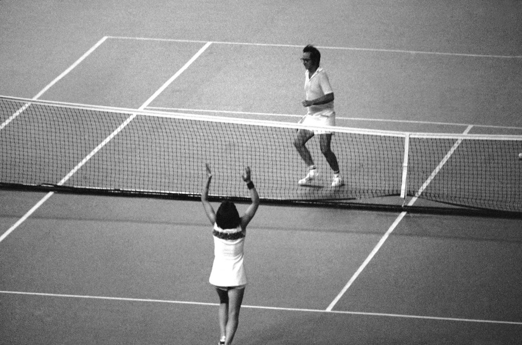 . Mrs. Billie Jean King raises her hands in triumph as her Opponent, Bobby Riggs, prepares to hurdle the net following her straight-set victory over him in tennis match at the Houston Astrodome in Houston on Sept. 20, 1973. (AP Photo)