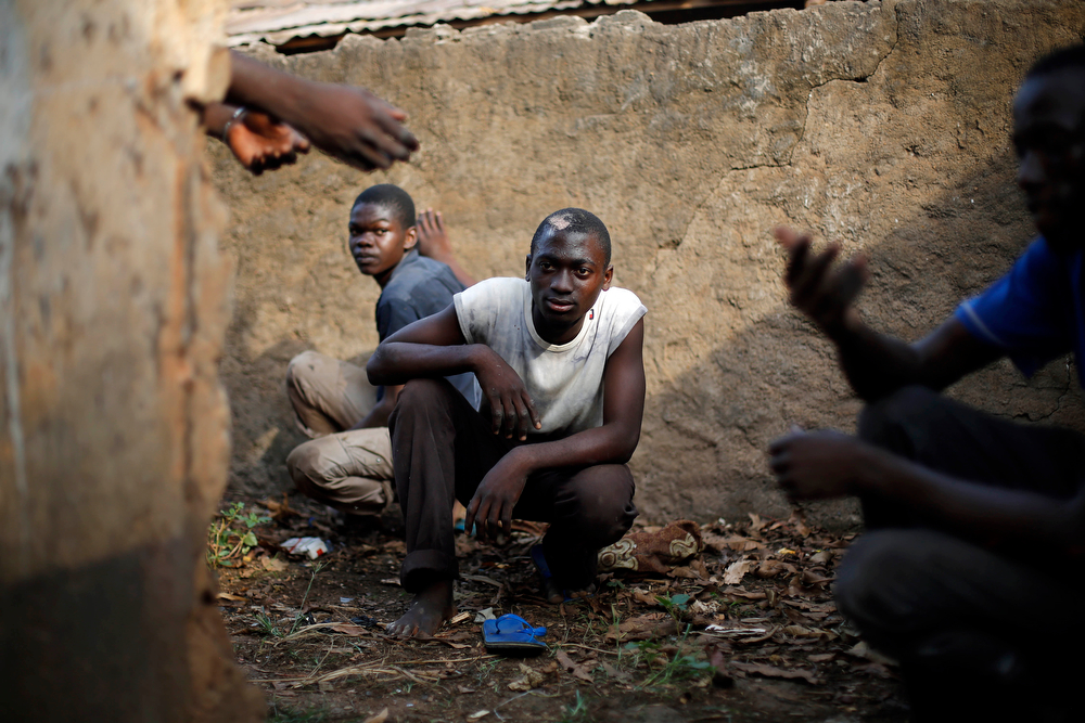 . Men take cover in a toilet as heavy gunfire erupts in the Miskin district of Bangui, Central African Republic, Monday Feb. 3, 2014. In what a French soldier on the scene described as the heaviest exchange of fire he\'d seen since early December 2013, Muslim militias engaged Burundi troops who returned fire. A third source of firing remained unidentified. Fighting between Muslim Seleka militias and Christian anti-Balaka factions continues as French and African Union forces struggle to contain the bloodshed. (AP Photo/Jerome Delay)
