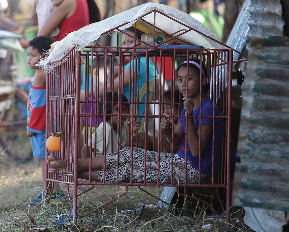 . Despite living in the massive typhoon aftermath, young girls get to play in a dog house in Tacloban, central Philippines, Friday, Nov. 15, 2013.  (AP Photo/Aaron Favila)