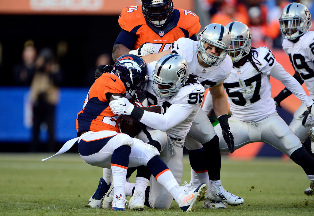 . DENVER, CO - DECEMBER 28: Ronnie Hillman (23) of the Denver Broncos gets hit at the line of scrimmage by Denico Autry (96) of the Oakland Raiders with no gain on the play in the second quarter.  The Denver Broncos played the Oakland Raiders at Sports Authority Field at Mile High in Denver on December, 28 2014. (Photo by Joe Amon/The Denver Post)