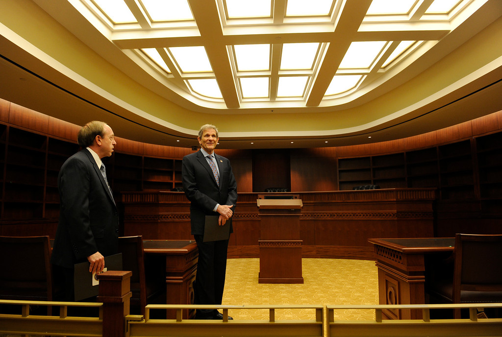 . Chief Justice Michael L. Bender, right, and the Colorado Attorney General John Suthers, stand inside a courtroom named the library courtroom, because it will be filled wall to wall with books. Construction crews put the finishing touches on the new Ralph L. Carr Colorado Judicial Center at 2 East 14th Avenue in Denver on Tuesday, Dec. 11, 2012. The courts will officially open at this location at 8 a.m. on Wed. Dec. 19, 2012. Kathryn Scott Osler, The Denver Post