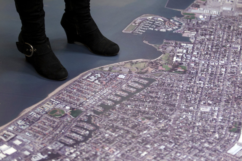. An unidentified woman stands by an aerial photograph of the city of Alameda, Calif. that greets visitors to the newly remodeled Permit Center inside City Hall, Wednesday, Nov. 6, 2013 in Alameda. (D. Ross Cameron/Bay Area News Group)