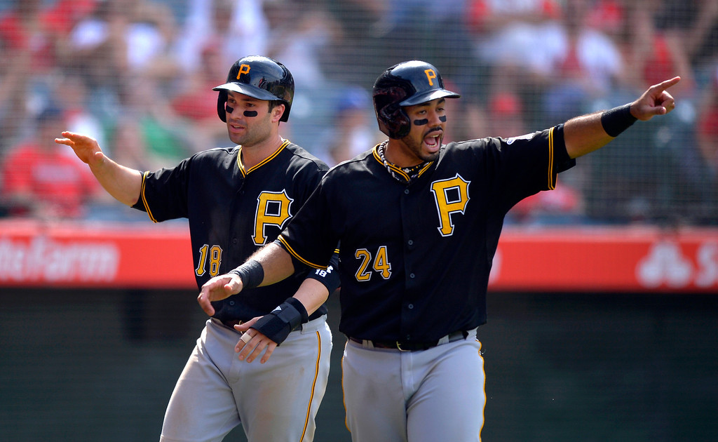 . Pittsburgh Pirates\' Pedro Alvarez, right, and Neil Walker celebrate after Alvarez scored on a single by Travis Snider and Walker scored on an error by Los Angeles Angels\' J.B. Shuck during the 10th inning of their baseball game, Sunday, June 23, 2013, in Anaheim, Calif.  (AP Photo/Mark J. Terrill)