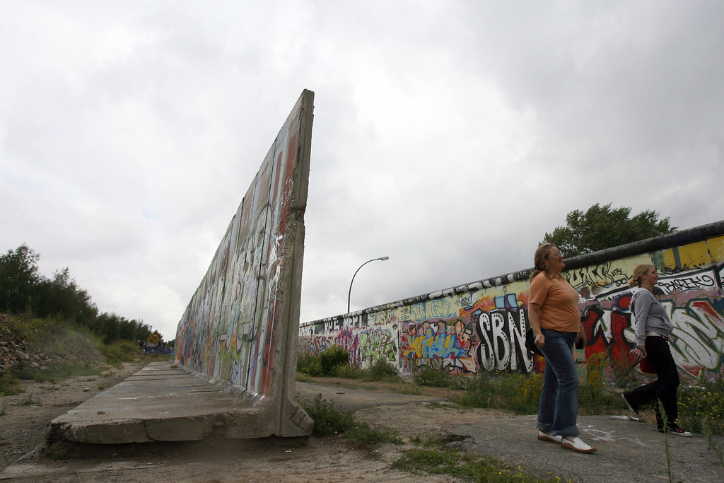 . Tourists walk past a portion of the Berlin wall (L) removed from the East Side Gallery in Berlin 23 August 2006. The east side gallery, a strip of the former Berlin wall that used to divide the city, has become a haven for painters, graffiti artists as well as anyone who feels an urge to express him or herself. (Photo credit JOHN MACDOUGALL/AFP/Getty Images)