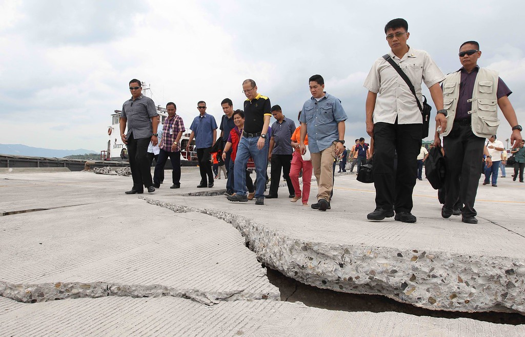 . In this handout photograph released by the Malacanang Photo Bureau, Philippine President Benigno Aquino (C, in black/yellow shirt) inspects an earthquake-damaged road at Tagbilaran City, Bohol, central Philippines, on October 16, 2013. AFP PHOTO/RYAN LIM/MALACANANG PHOTO BUREAU/AFP/Getty Images