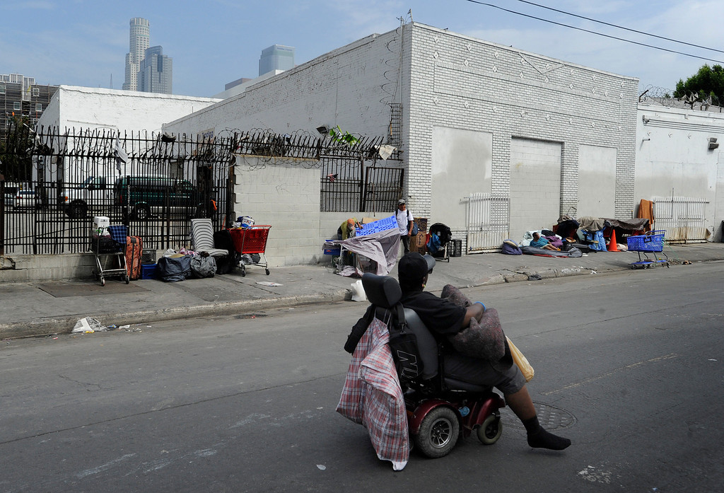 . Homeless people congregate in this area of San Julian Street between 7th and 8th streets in Los Angeles.  Representatives from government agencies, nonprofit organizations, charities and businesses will gather Friday for a summit on citywide homelessness. They\'ll discuss the effectiveness of relatively new strategies for reducing homelessness, including providing permanent supportive housing for the most vulnerable, and a pilot project for those on Skid Row.  .Los Angeles, CA. 7/11/2013 (John McCoy/LA Daily News)