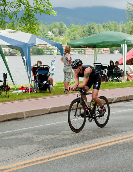IronmanLP-20 - Flying by Mirror Lake at the end of the first bike circuit. The swim course bouys are visible in the lake, and the town of Lake Placid is across the lake.