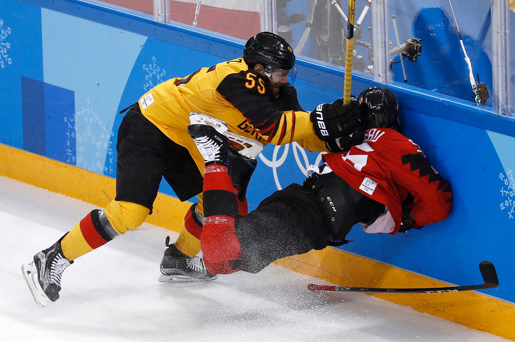 . Felix Schutz (55), of Germany, slams Maxim Noreau (56), of Canada, into the wall during the first period of the semifinal round of the men\'s hockey game at the 2018 Winter Olympics in Gangneung, South Korea, Friday, Feb. 23, 2018. (AP Photo/Patrick Semansky)