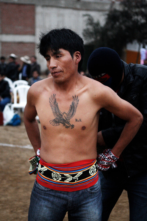 . Dionisio Colquemarca prepares to fight in a Takanakuy ritual fight in Lima, Peru.  Often with faces swollen and bloodied, the fighters shake hands or hug and deem their personal dispute settled. Or else they agree to do battle again next year. (AP Photo/Karel Navarro)
