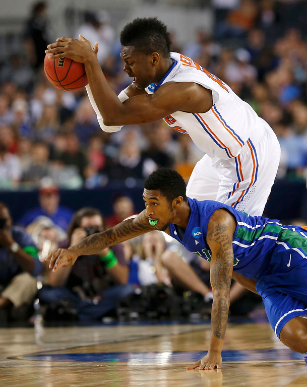. Florida Gulf Coast Eagles guard Dajuan Graf (lower) lunges for the ball with Florida Gators forward Will Yeguete during the first half in their South Regional NCAA men\'s basketball game in Arlington, Texas March 29, 2013. REUTERS/Jim Young