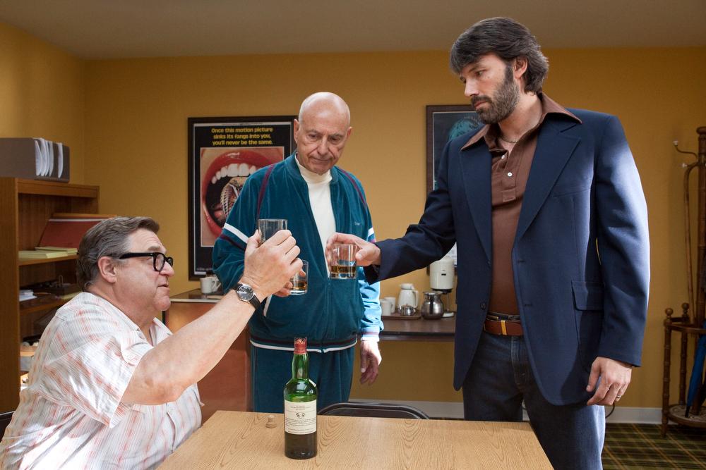 ". This image released by Warner Bros shows John Goodman, left, Alan Arkin, center, and actor-director Ben Affleck in a scene from ""Argo.\""  Affleck was nominated Thursday, Dec. 13, 2012 for a Golden Globe for best director for the film. Arkin was also nominated for best supporting actor for his role in the film. The 70th annual Golden Globe Awards will be held on Jan. 13. (AP Photo/Warner Bros., Claire Folger)"