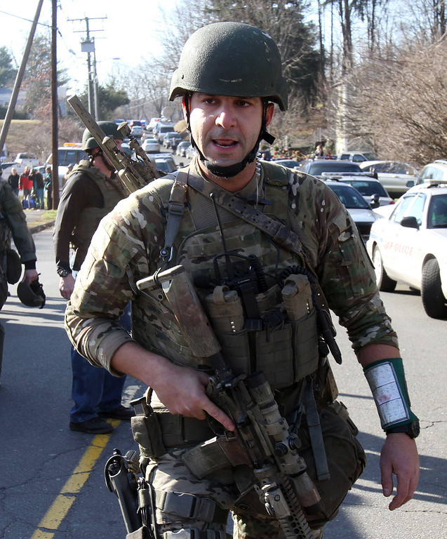 . Heavily armed Connecticut State troopers are on the scene at the Sandy Hook School following a shooting at the school, Friday, Dec. 14, 2012 in Newtown, Conn. A man opened fire inside the Connecticut elementary school where his mother worked Friday, killing 26 people, including 18 children, and forcing students to cower in classrooms and then flee with the help of teachers and police. (AP Photo/The Journal News, Frank Becerra Jr.)