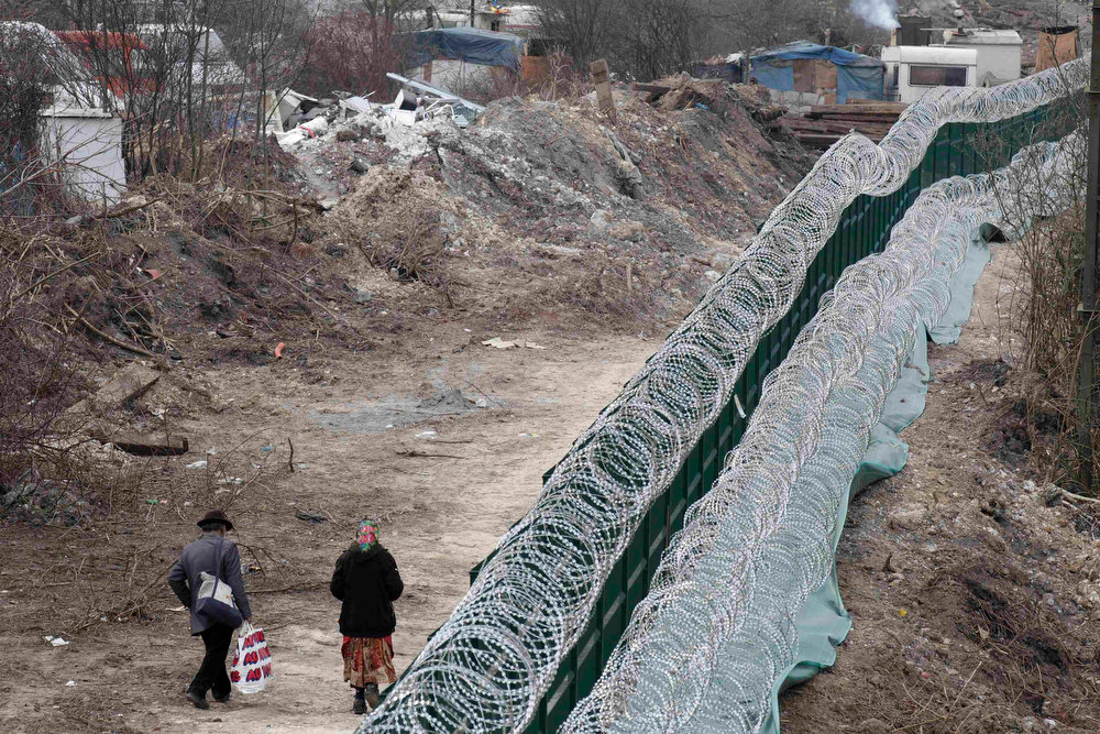 . A Roma couple walks past a razor barbed wire fence as they return to their illegal camp in Lille during International Roma Day on April 8, 2013. French authorities built this fence last week to prevent that the Roma from crossing the railway tracks to join another camp.   REUTERS/Pascal Rossignol