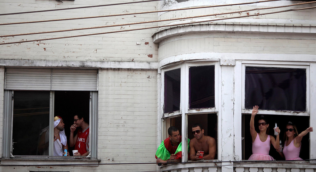 ". Revelers stand at windows as they observe the annual block party known as the ""Suvaco do Cristo\"" (Armpit of Christ), one of the many pre-carnival parties to take place in the neighborhoods of Rio de Janeiro February 3, 2013. REUTERS/ Ricardo Moraes"