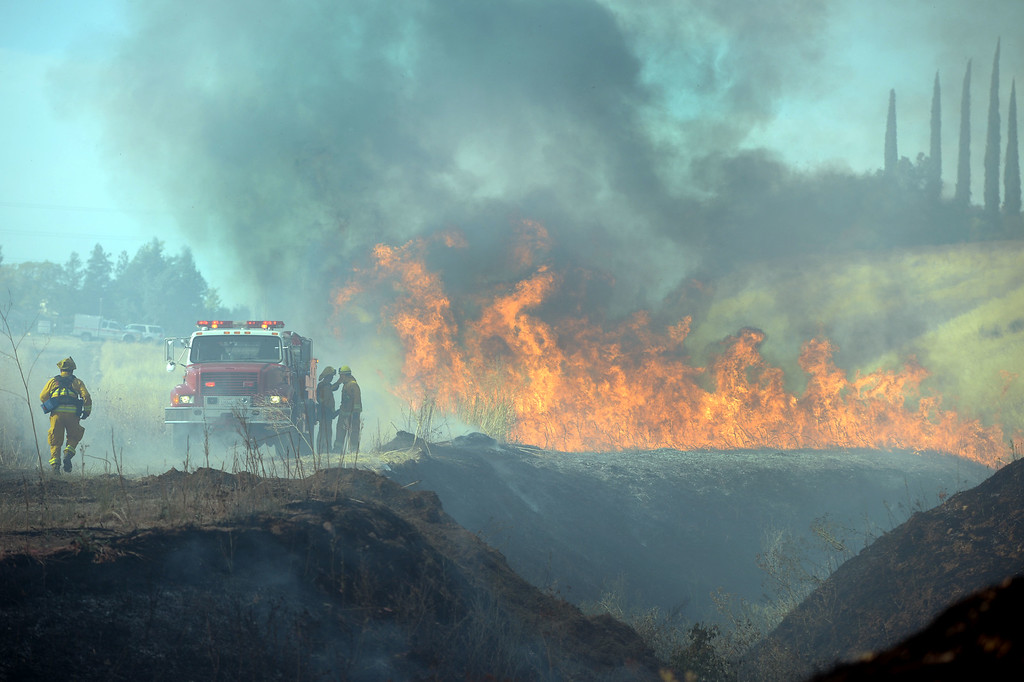 . Firefighters start to lay a hose near a vegetation fire near Foothill Drive where a blue sky is filled with smoke in Antioch, Calif., on Wednesday, June 24, 2015. (Susan Tripp Pollard/Bay Area News Group)