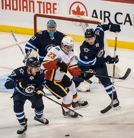 DAVID LIPNOWSKI / WINNIPEG FREE PRESS  Winnipeg Jets #27 Nikolaj Ehlers and #8 Jacob Trouba get between Calgary Flames #23 Sean Monahan Thursday December 27, 2018 at Bell MTS Place.
