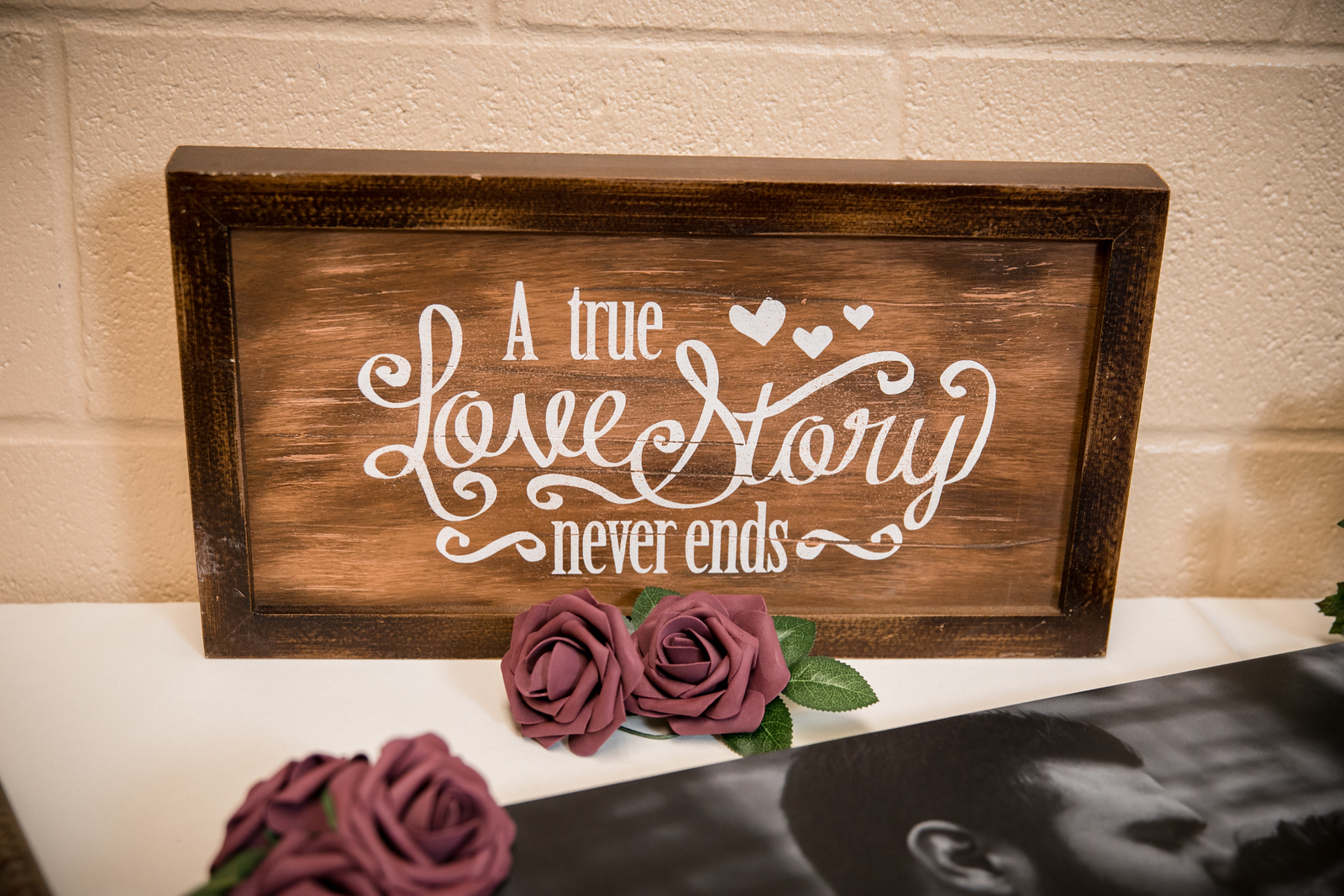 A rustic wood sign that reads 'A True Love Story Never Ends'