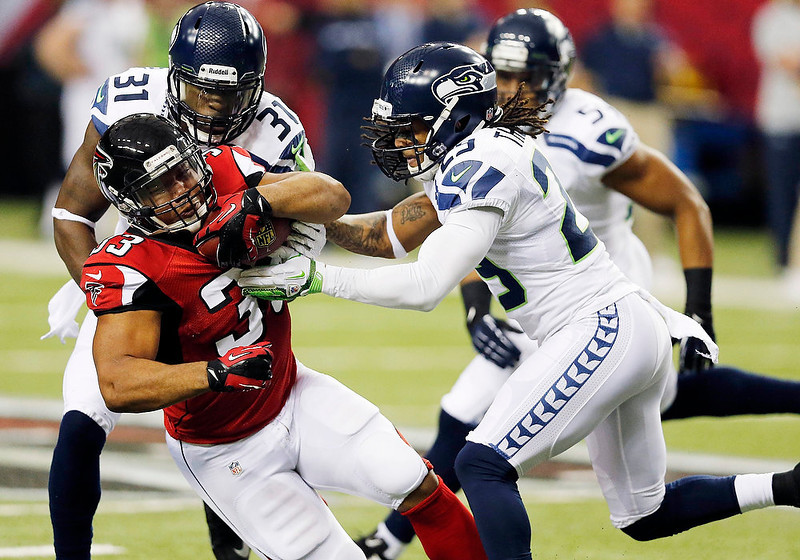 . Atlanta Falcons running back Michael Turner (33) his hit by Seattle Seahawks free safety Earl Thomas (29) and Seattle Seahawks strong safety Kam Chancellor (31) during the first half of an NFC divisional playoff NFL football game Sunday, Jan. 13, 2013, in Atlanta. (AP Photo/John Bazemore)