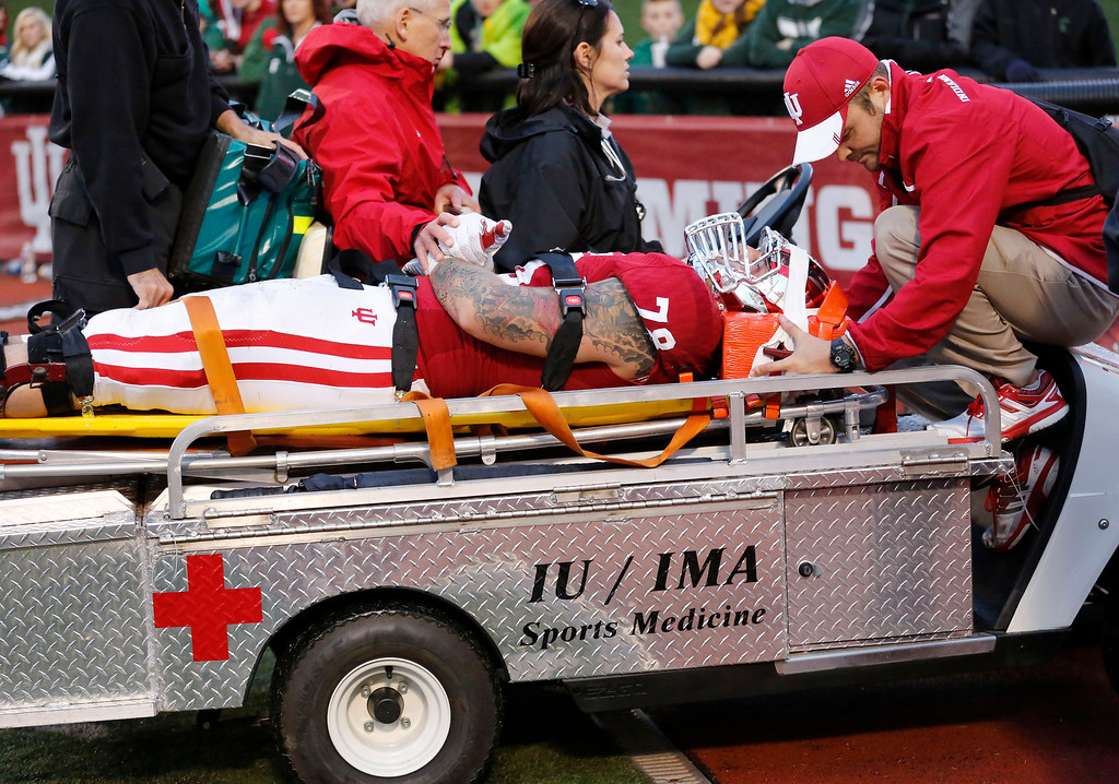 . Indiana offensive tackle Jason Spriggs (78) is taken off the field on a backboard and cart in the second half of an NCAA college football game in Bloomington, Ind., Saturday, Oct. 18, 2014. Michigan State won the game 56-17. (AP Photo/Sam Riche)