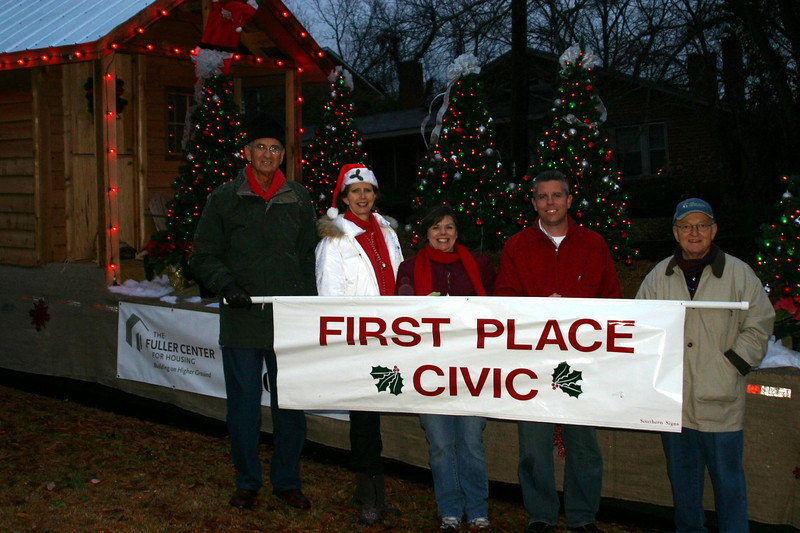 08 12-11 Chattahoochee Fuller Center float wins first place in Christmas Parade thanks to Julie & Joey Ambrose.  Partner families had the joy of riding it in the parade. L-R: Millard & Linda Fuller, Julie & Joey Ambrose and Bill Scott. Lynda Spofford