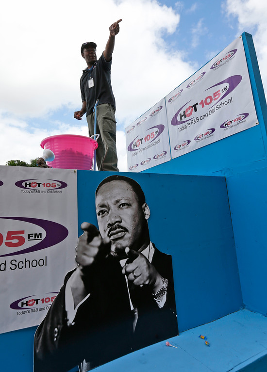 . Rodney Baltimore points to people in the crowd as he tosses candy during a parade honoring Dr. Martin Luther King Jr., Monday, Jan. 16, 2017, in the Liberty City neighborhood of Miami. (AP Photo/Wilfredo Lee)