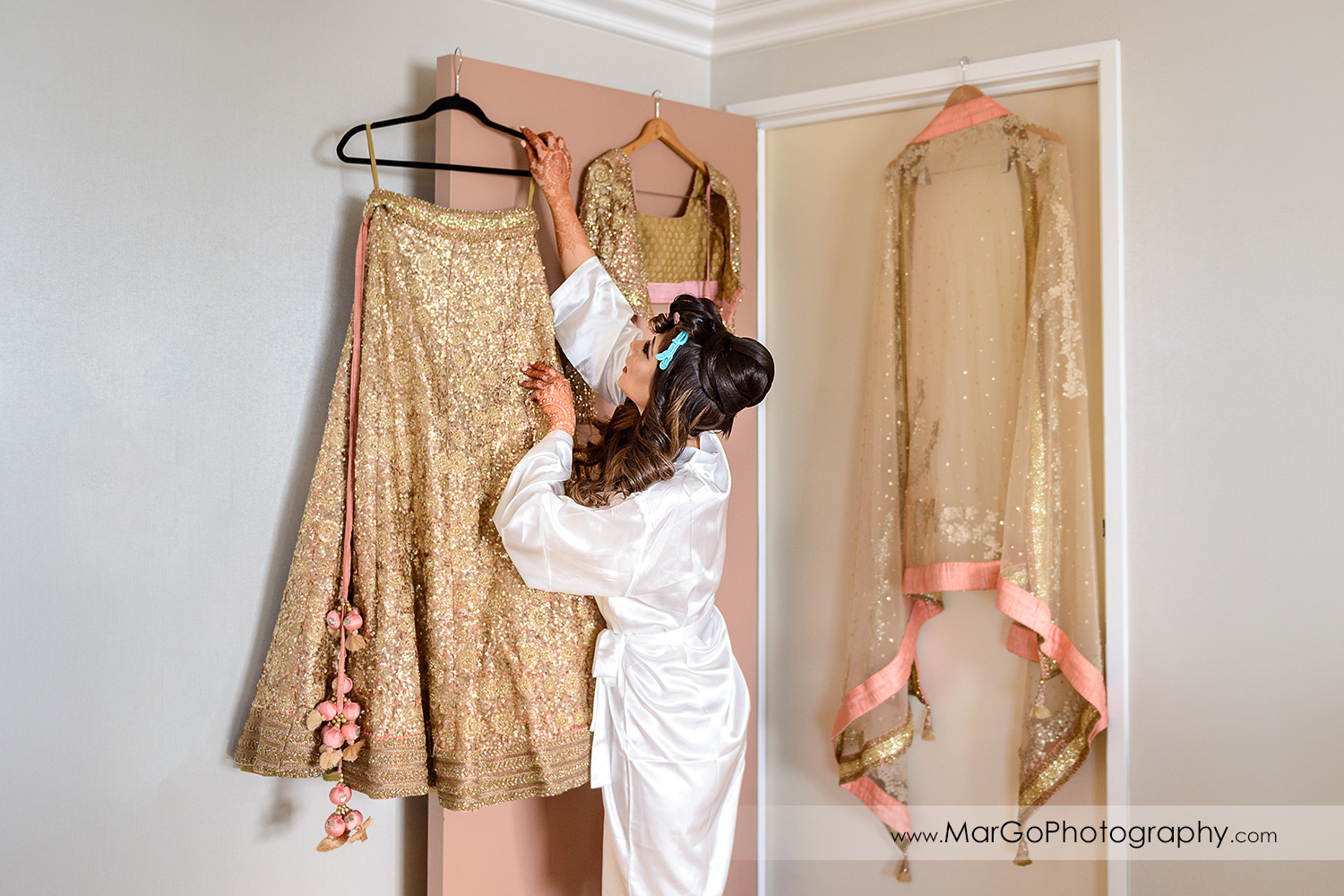 bride reaching for indian wedding dress at DoubleTree by Hilton Pleasanton at the Club
