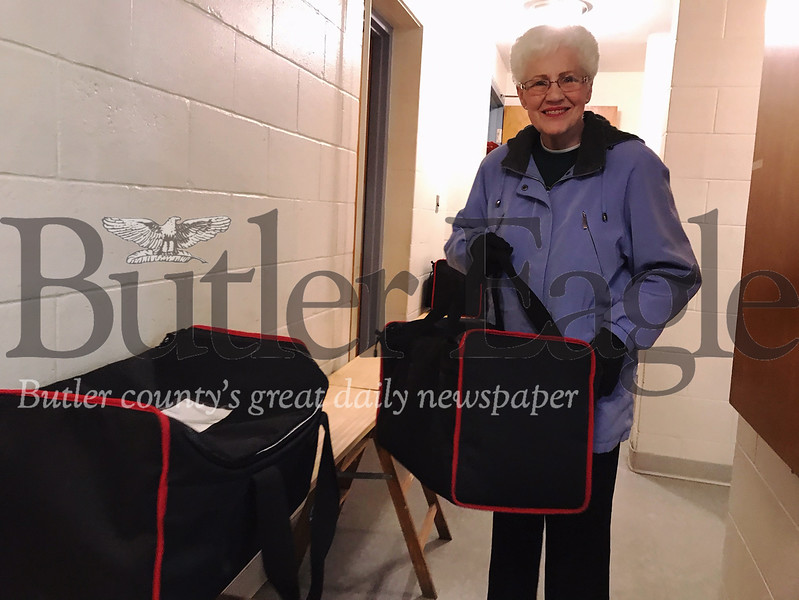 Butler resident Peggy Loomis, who has volunteered with Butler Meals on Wheels since 1970, picks up her pack of hot meals to deliver Tuesday. The organization celebrates 50 years of service this year.