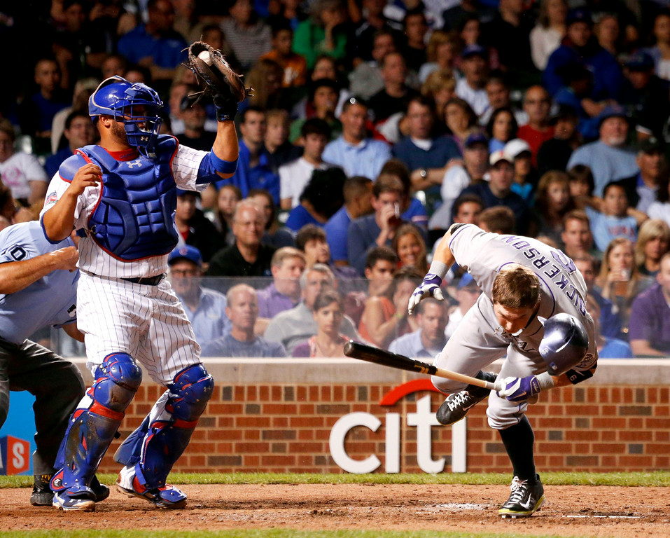 . Colorado Rockies\' Corey Dickerson reacts to a high pitch from Chicago Cubs\' Edwin Jackson, as catcher Welington Castillo grabs the ball, during the fourth inning of a baseball game Tuesday, July 29, 2014, in Chicago. (AP Photo/Charles Rex Arbogast)