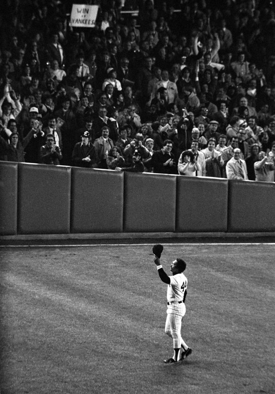 . New York Yankees slugger Reggie Jackson acknowledges the fans\' tribute as he returns to his outfield position in the top of the ninth inning of the final World Series game against the Los Angeles Dodgers at New York\'s Yankee Stadium in the Bronx, Tuesday night, Oct. 18, 1977.  Jackson slammed his third consecutive home run of the game to give the Bronx Bombers their 8-4 victory for the championship.  (AP Photo)