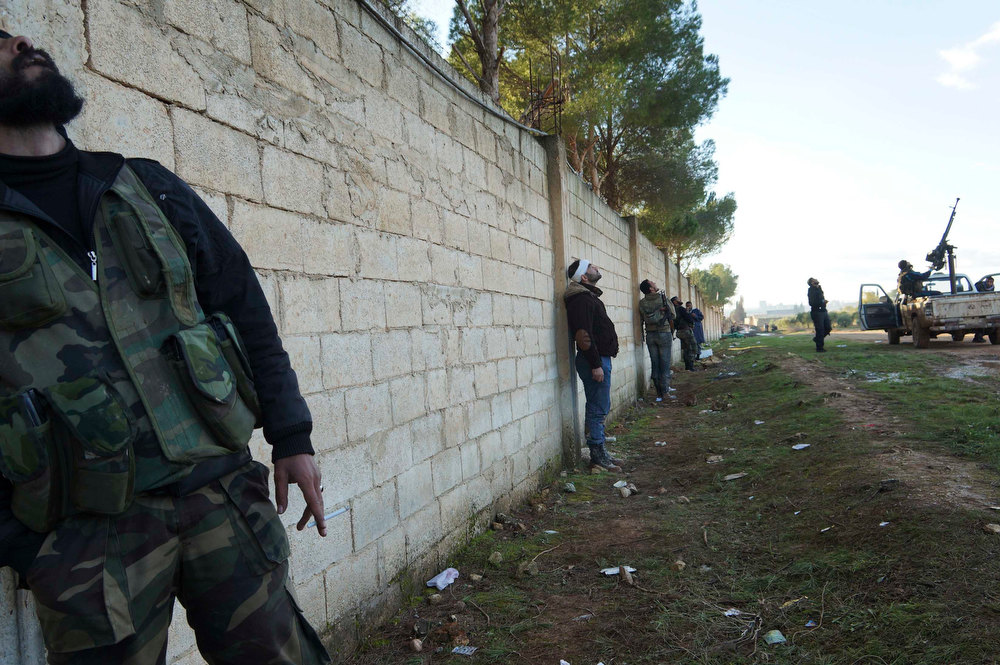 . Free Syrian Army fighters take up positions during an airstrike in Aleppo\'s al-Amereya district December 12, 2012. Picture taken December 12, 2012. REUTERS/Saleh Anadani