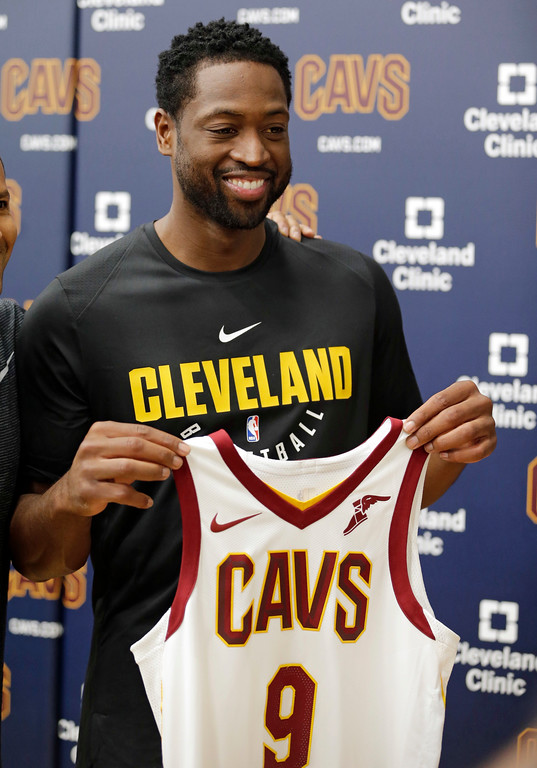. Cleveland Cavaliers\' Dwyane Wade holds up his jersey during a news conference at the NBA basketball team\'s training facility, Friday, Sept. 29, 2017, in Independence, Ohio. Wade once convinced LeBron James that Miami was the place to be. Seven years later, James lured Wade to Ohio for the chance to win another NBA title, together.(AP Photo/Tony Dejak)