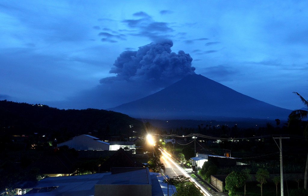 . A view of Mount Agung volcano erupting in Karangasem, Bali, Indonesia, Tuesday, Nov. 28, 2017. Indonesia authorities raised the alert for the rumbling volcano to highest level on Monday and closed the international airport on tourist island of Bali stranding thousands of travelers. (AP Photo/Firdia Lisnawati)
