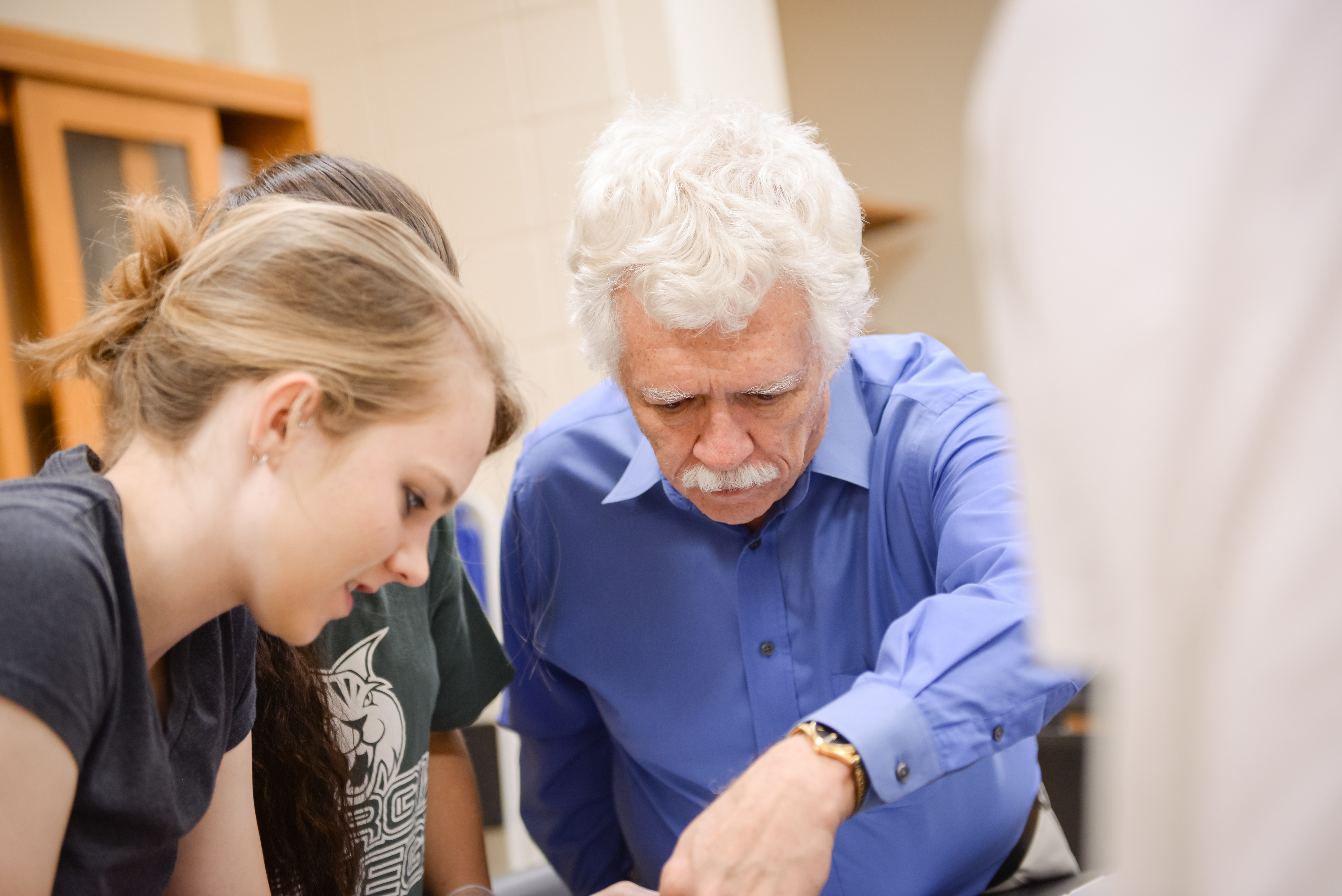 Dr. Saladin works with biology students in the lab.