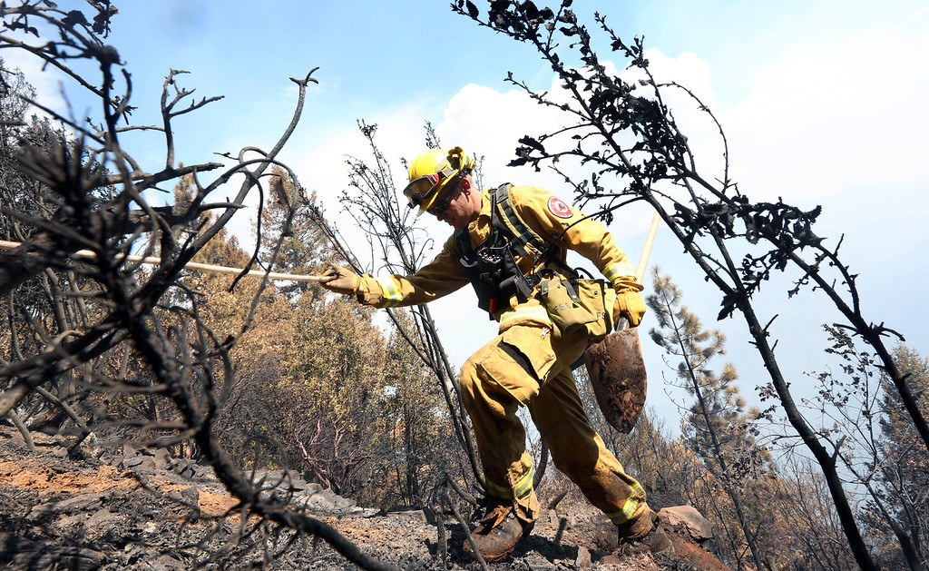 . Firefighter Jesse Hadorowski climbs up steep terrain while battling a fire near Pollack Pines, Calif., Monday, Sept. 15, 2014. The fire, which started Sunday has consumed more than 3,000 acres and forced the evacuation of dozens of homes.(AP Photo/Rich Pedroncelli)