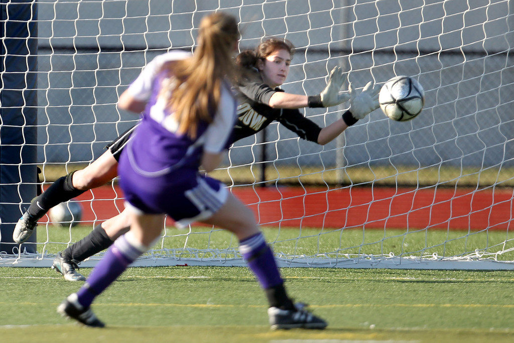 . Piedmont\'s Erin Greening (17) kicks the last penalty kick as Bishop O\'Dowd goalie Lorna McElrath (1) dives to her left to make a save to claim the North Coast Section Division II Girls Soccer Championship at Dublin High School soccer field in Dublin, Calif., on Saturday, Feb. 23, 2013. Bishop O\'Dowd won 3-2 in a series of penalty kicks. (Ray Chavez/Staff)