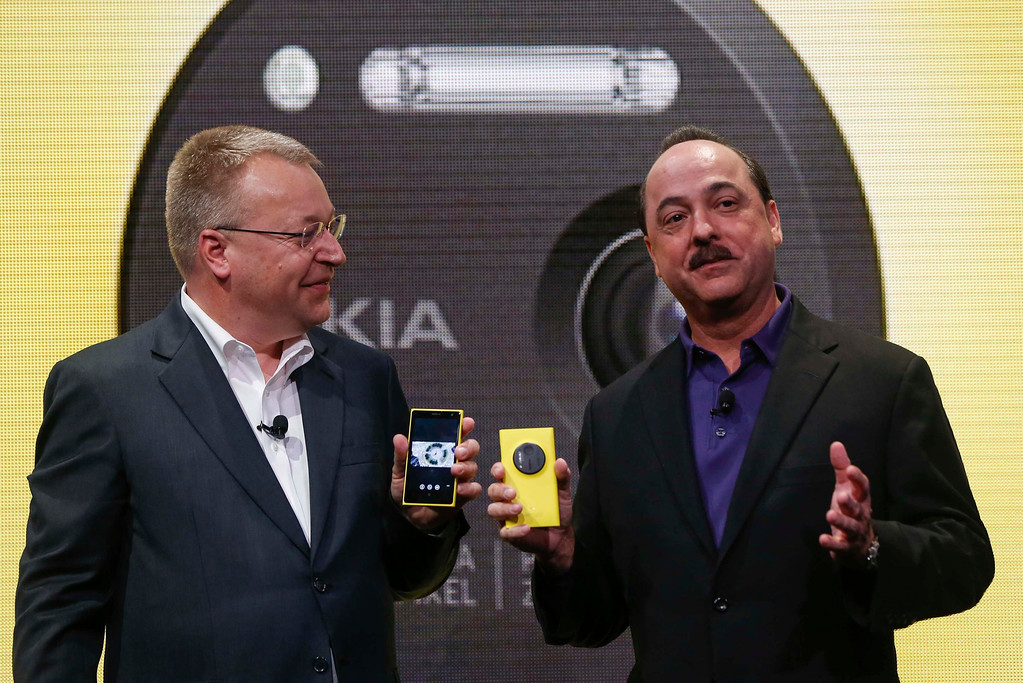 . AT&T Mobility President and Chief Executive Ralph de la Vega (R) takes the stage with Nokia Chief Executive Stephen Elop as Elop unveils Nokia\'s new smartphone, the Lumia 1020 with a 41-megapixel camera, in New York July 11, 2013.   REUTERS/Shannon Stapleton