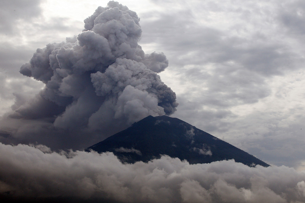 . Clouds of ashes rise from the Mount Agung volcano erupting in Karangasem, Bali, Indonesia, Tuesday, Nov. 28, 2017. Indonesia authorities raised the alert for the rumbling volcano to highest level on Monday and closed the international airport on the tourist island of Bali stranding thousands of travelers. (AP Photo/Firdia Lisnawati)
